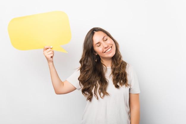 La giovane donna sorridente con gli occhi chiusi sta tenendo un fumetto giallo.