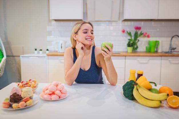 Giovane donna sorridente con la mela verde in una mano scegliendo tra cibo sano e malsano in cucina. scelta difficile tra frutta fresca o dolci.
