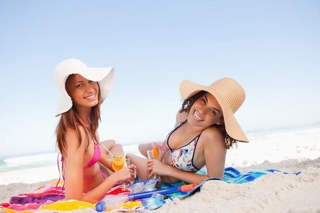 Giovani donne sorridenti che si trovano sui teli da spiaggia mentre guardando la telecamera