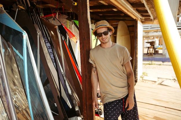 Giovane sorridente giovane uomo in cappello e occhiali da sole in piedi presso la baracca di surf
