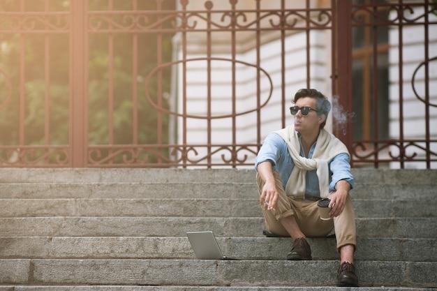 Giovane uomo fumatori in pausa caffè su sfondo urbano. cattive abitudini. stile di vita malsano, vita studentesca moderna, concetto hipster