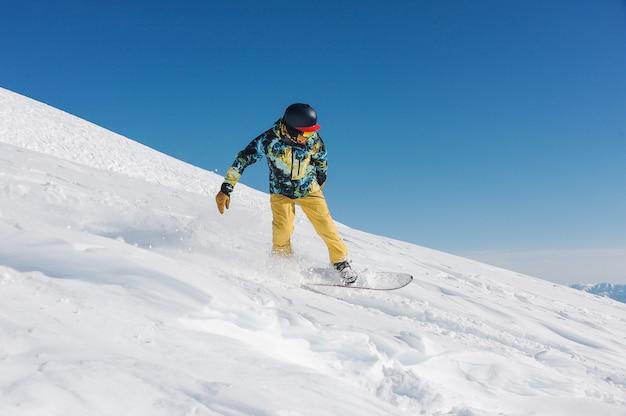 Giovane snowboarder in abbigliamento sportivo alla moda che guida giù per il pendio in georgia, gudauri