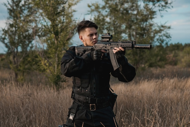 Giovane soldato in uniforme nera che mira un fucile d'assalto