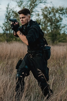 Giovane soldato in uniforme nera che mira una pistola