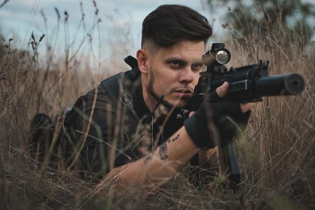 Giovane soldato in uniforme nera sdraiato e puntando un fucile d'assalto