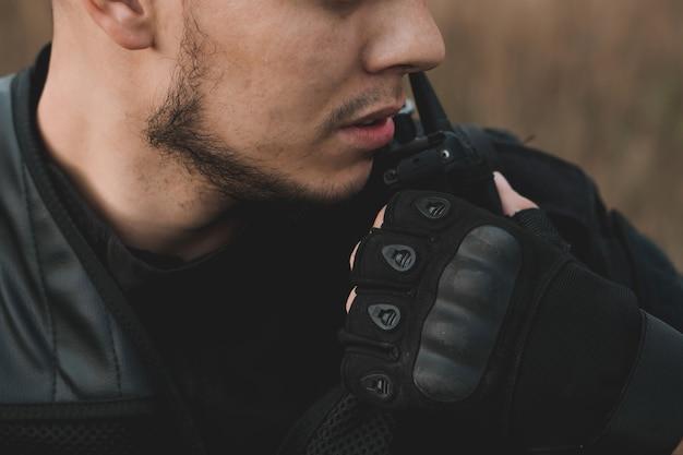Giovane soldato in uniforme nera che fa rapporto alla radio