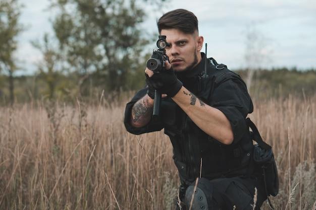 Giovane soldato in uniforme nera che si siede e mira con un fucile d'assalto