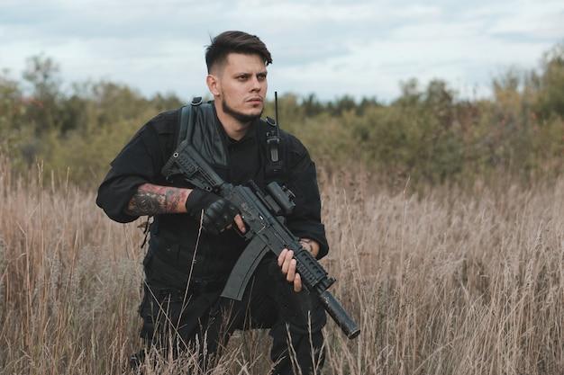 Giovane soldato in uniforme nera che si siede con un fucile d'assalto
