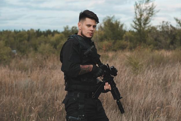 Giovane soldato in uniforme nera con un fucile d'assalto