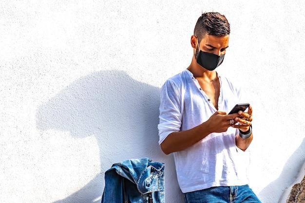 Giovane viaggiatore solitario che si appoggia a un muro bianco con la borsa del trolley utilizzando lo smartphone che chiacchiera online in attesa di autobus o treno indossando la maschera protettiva nera del coronavirus. ragazzo moderno in colori vivaci effetto vivido
