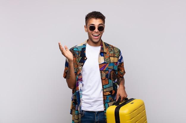 Giovane uomo sudamericano che si sente felice, sorpreso e allegro, sorridente con atteggiamento positivo, realizzando una soluzione o un'idea