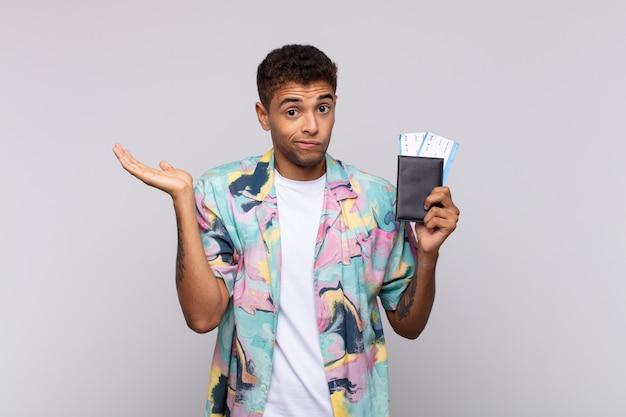 Giovane uomo sudamericano sentendosi perplesso e confuso, dubitando, ponderando o scegliendo diverse opzioni con un'espressione divertente