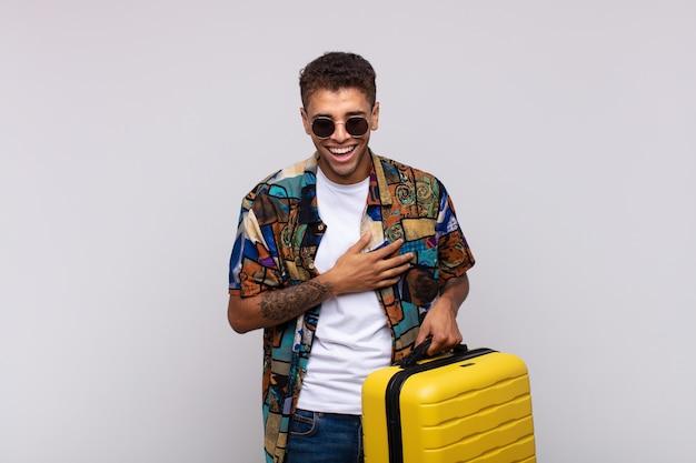 Giovane uomo sudamericano che ride ad alta voce a uno scherzo esilarante, sentendosi felice e allegro, divertendosi