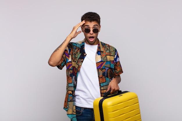 Giovane uomo sudamericano che sembra felice, stupito e sorpreso, sorridente e realizzando incredibili e incredibili buone notizie