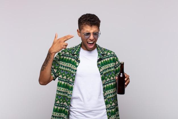 Giovane uomo sudamericano che sembra infelice e stressato, gesto di suicidio che fa il segno della pistola con la mano, indicando la testa