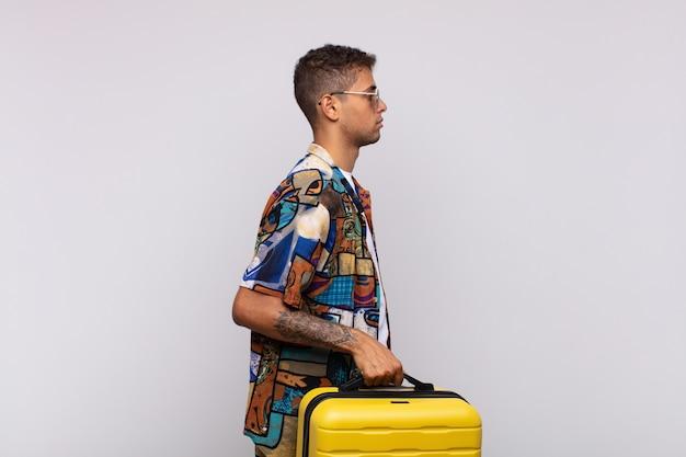 Giovane uomo sudamericano sulla vista di profilo che cerca di copiare lo spazio davanti, pensare, immaginare o sognare ad occhi aperti