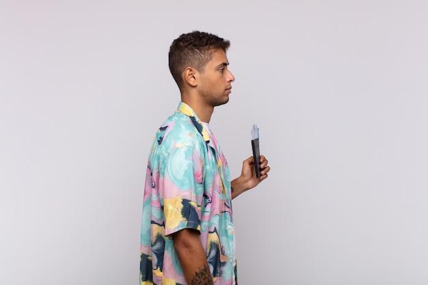 Giovane uomo sudamericano sulla vista di profilo che cerca di copiare lo spazio davanti, pensare, immaginare