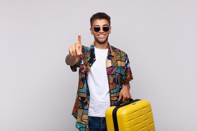Giovane uomo sudamericano che sorride e che sembra amichevole, mostrando il numero uno o il primo con la mano in avanti, contando alla rovescia