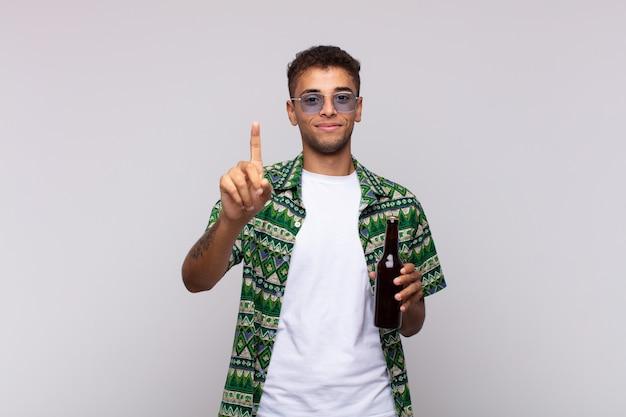 Giovane uomo sudamericano che sorride e sembra amichevole, mostrando il numero uno o il primo con la mano in avanti, contando alla rovescia