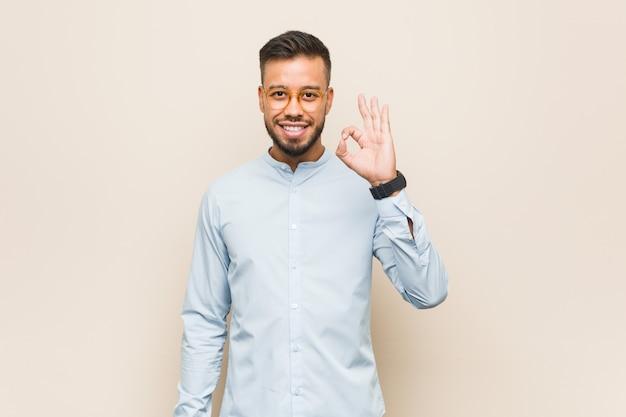 Giovane uomo d'affari sud-asiatico allegro e fiducioso mostrando gesto ok.