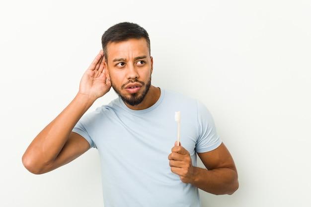 Giovane uomo sud-asiatico che tiene uno spazzolino da denti cercando di ascoltare un pettegolezzo.