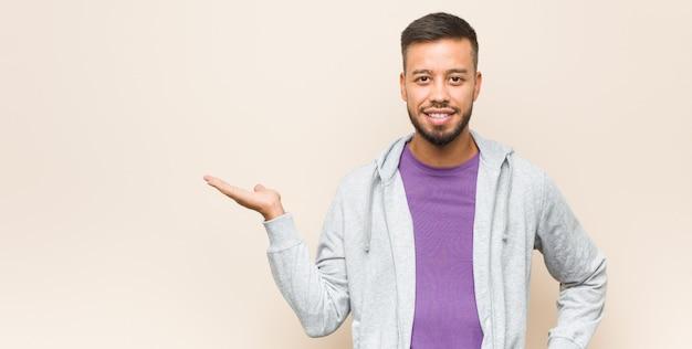 Giovane uomo sud-asiatico che mostra uno spazio di copia sul palmo e che tiene un'altra mano sulla vita.