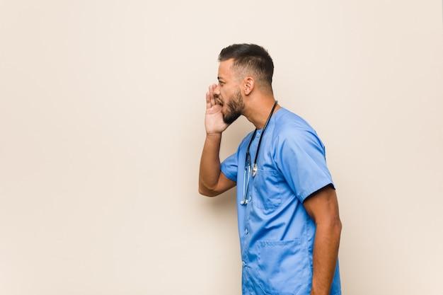 Giovane uomo sud-asiatico dell'infermiera che grida e che tiene il palmo vicino alla bocca aperta.