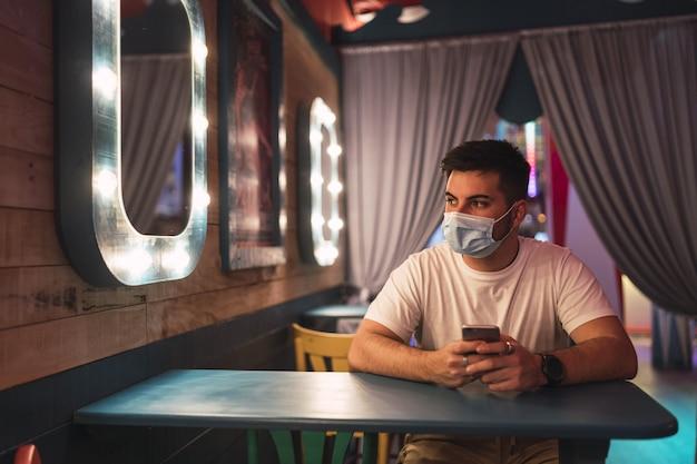 Il giovane ragazzo spagnolo che indossa una maschera facciale è seduto in un caffè; vita sociale durante la pandemia