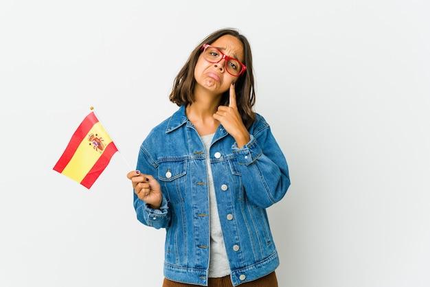 Giovane donna spagnola che tiene una bandiera isolata su sfondo bianco piangendo, insoddisfatta di qualcosa, agonia e concetto di confusione.