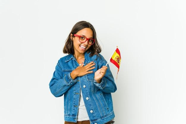 La giovane donna spagnola che tiene una bandiera isolata sul muro bianco ha un'espressione amichevole, premendo il palmo sul petto