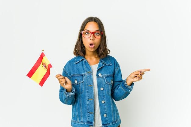 Giovane donna spagnola che tiene una bandierina isolata sulla parete bianca che indica al lato