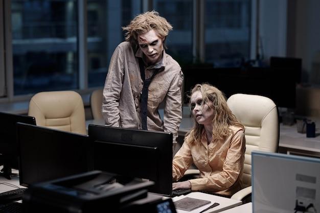 Giovane imprenditore zombie spettrale in piedi accanto alla collega seduta alla scrivania davanti al monitor del computer durante il lavoro di squadra