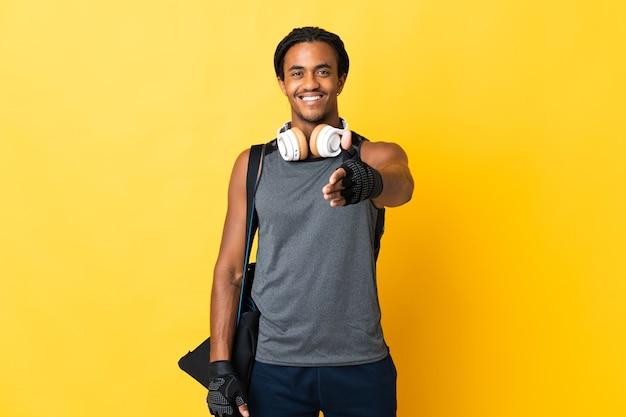 Young sport uomo afroamericano con trecce con borsa isolato su sfondo giallo si stringono la mano per chiudere un buon affare