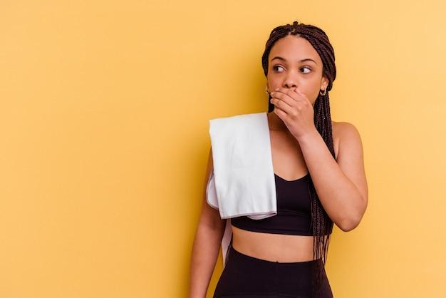 Giovane donna afroamericana di sport che tiene un tovagliolo isolato sulla parete gialla premurosa che osserva ad uno spazio della copia che copre la bocca con la mano