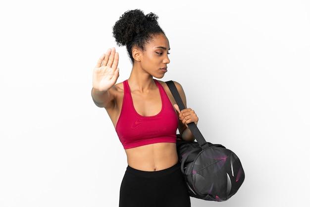 Giovane donna afroamericana sportiva con borsa sportiva isolata su sfondo blu che fa gesto di arresto e delusa