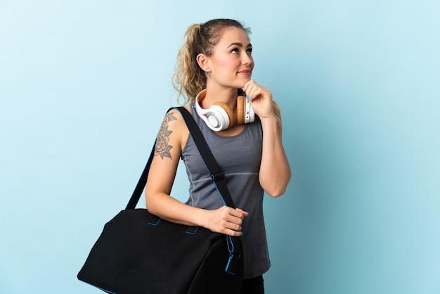 Giovane donna brasiliana sportiva con borsa sportiva isolata su sfondo blu e alzando lo sguardo