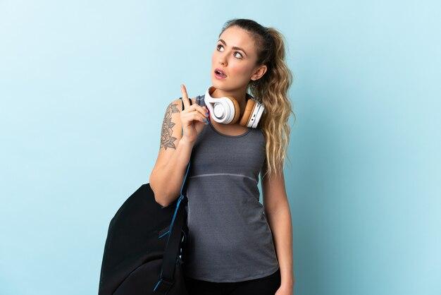 Young sport donna brasiliana con borsa sportiva isolata su sfondo blu pensando un'idea puntando il dito verso l'alto
