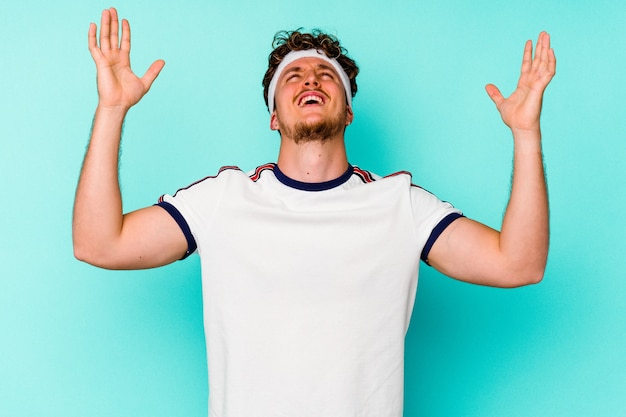 Giovane uomo caucasico sportivo isolato su sfondo blu che urla al cielo, alzando lo sguardo, frustrato.
