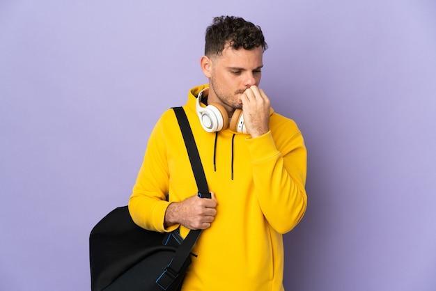 Uomo caucasico di giovane sport con la parete viola isolata borsa che ha dubbi