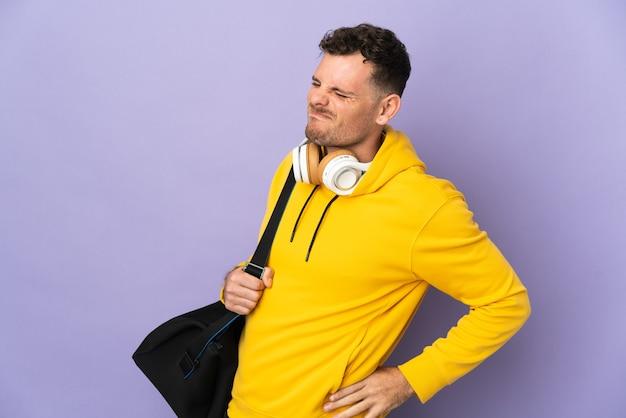 Uomo caucasico di giovane sport con muro viola isolato borsa che soffre di mal di schiena per aver fatto uno sforzo