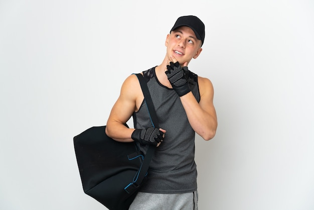 Giovane uomo caucasico di sport con la borsa isolata sulla parete bianca che osserva in su mentre sorride