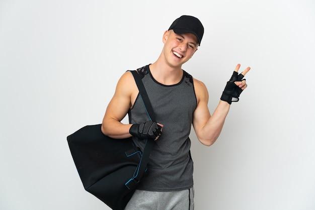 Uomo caucasico di giovane sport con la borsa isolata sulla parete bianca che sorride e che mostra il segno di vittoria