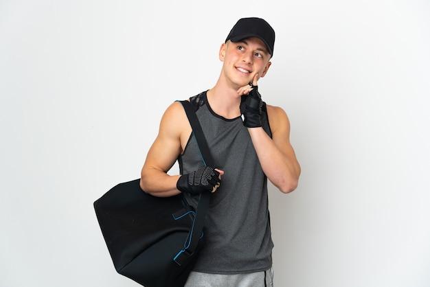 Giovane uomo caucasico di sport con la borsa isolata sulla parete bianca che pensa un'idea mentre osserva in su