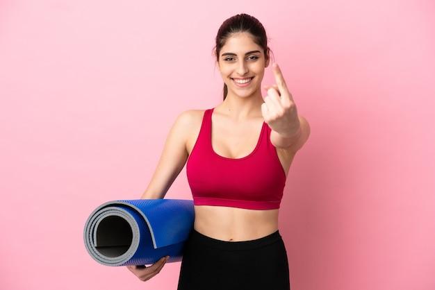 Giovane donna caucasica sportiva che va alle lezioni di yoga mentre tiene in mano un tappetino facendo un gesto imminente