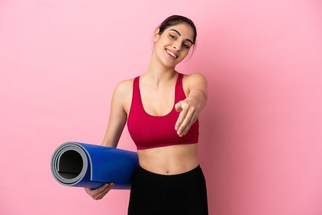 Giovane donna caucasica sportiva che va alle lezioni di yoga tenendo un tappetino che stringe la mano per chiudere un buon affare