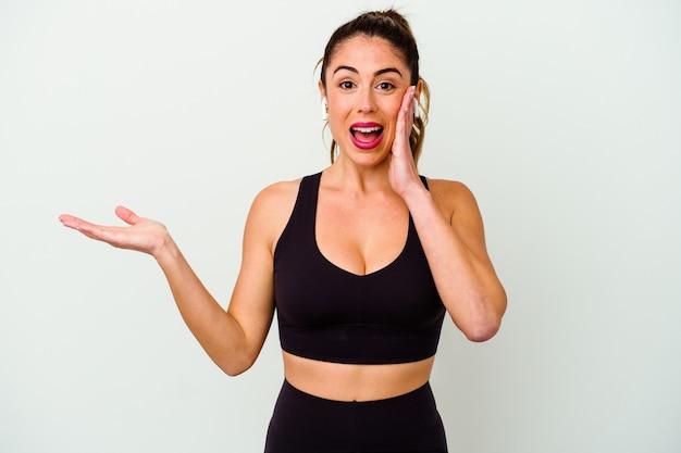 La giovane donna caucasica sportiva isolata su bianco tiene lo spazio della copia su un palmo, tiene la mano sulla guancia. stupito e deliziato.