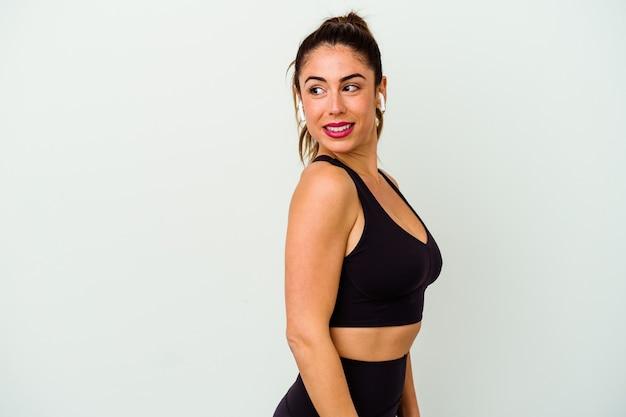 La giovane donna caucasica sportiva isolata su bianco guarda da parte sorridente, allegra e piacevole.