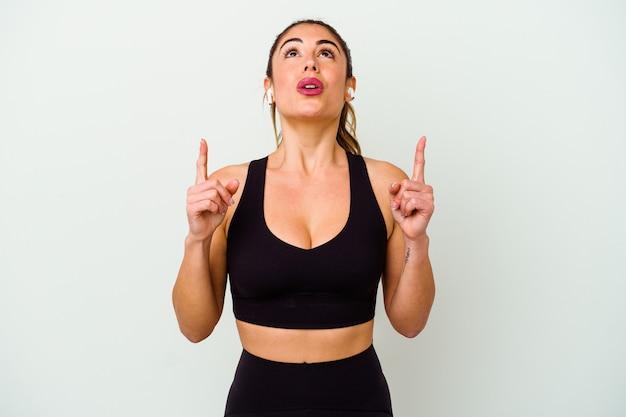 Giovane donna caucasica sportiva isolata su bianco che punta al rialzo con la bocca aperta.