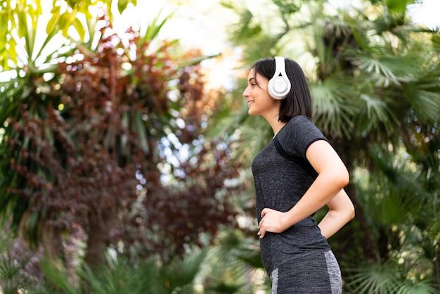 Donna caucasica di giovane sport che ascolta la musica con le cuffie all'aperto in un parco