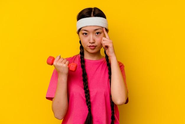 Giovane donna cinese di sport isolata sul tempiale di puntamento del fondo giallo con il dito, pensando, messo a fuoco su un compito.